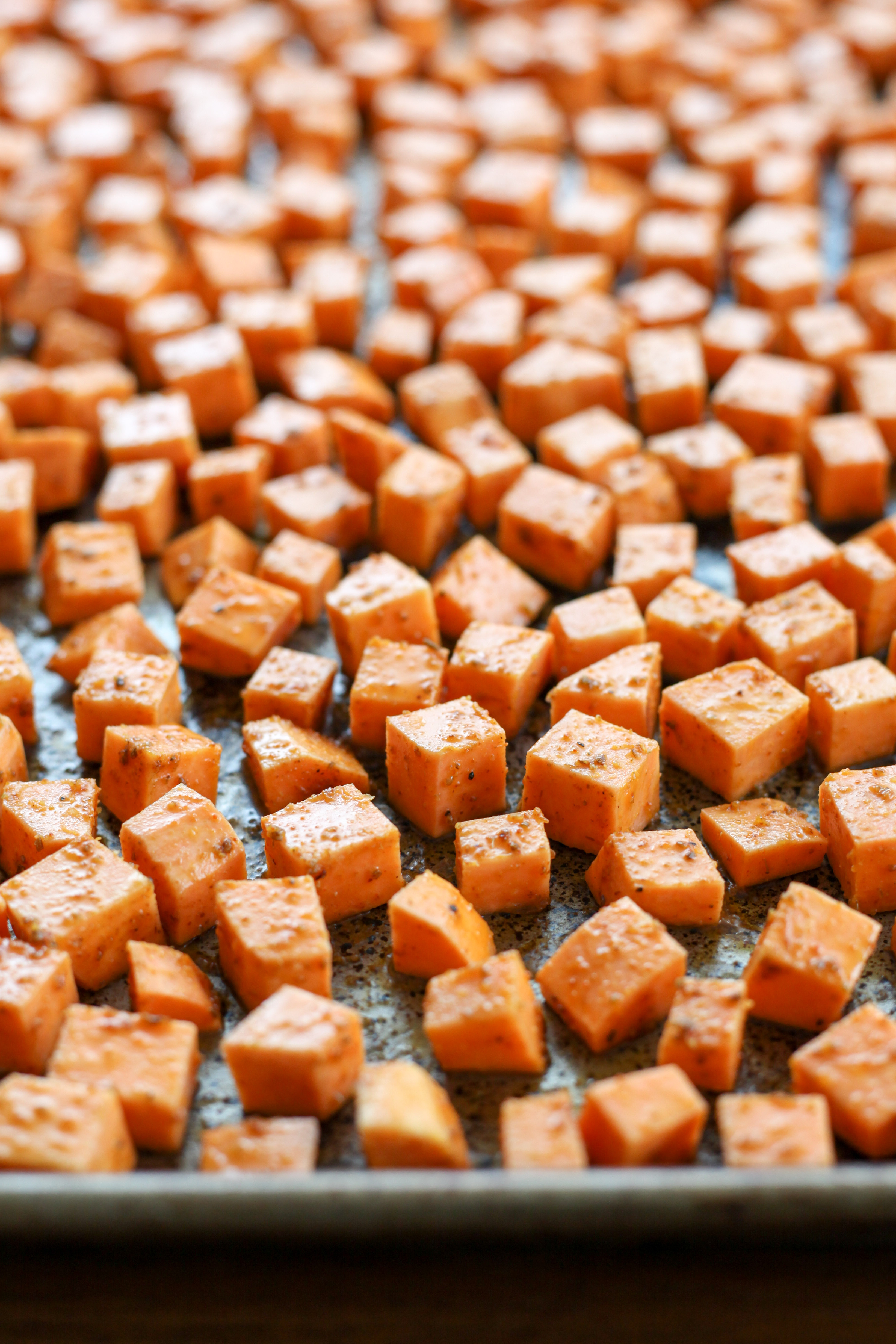 Diced spiced sweet potatoes, ready to be roasted