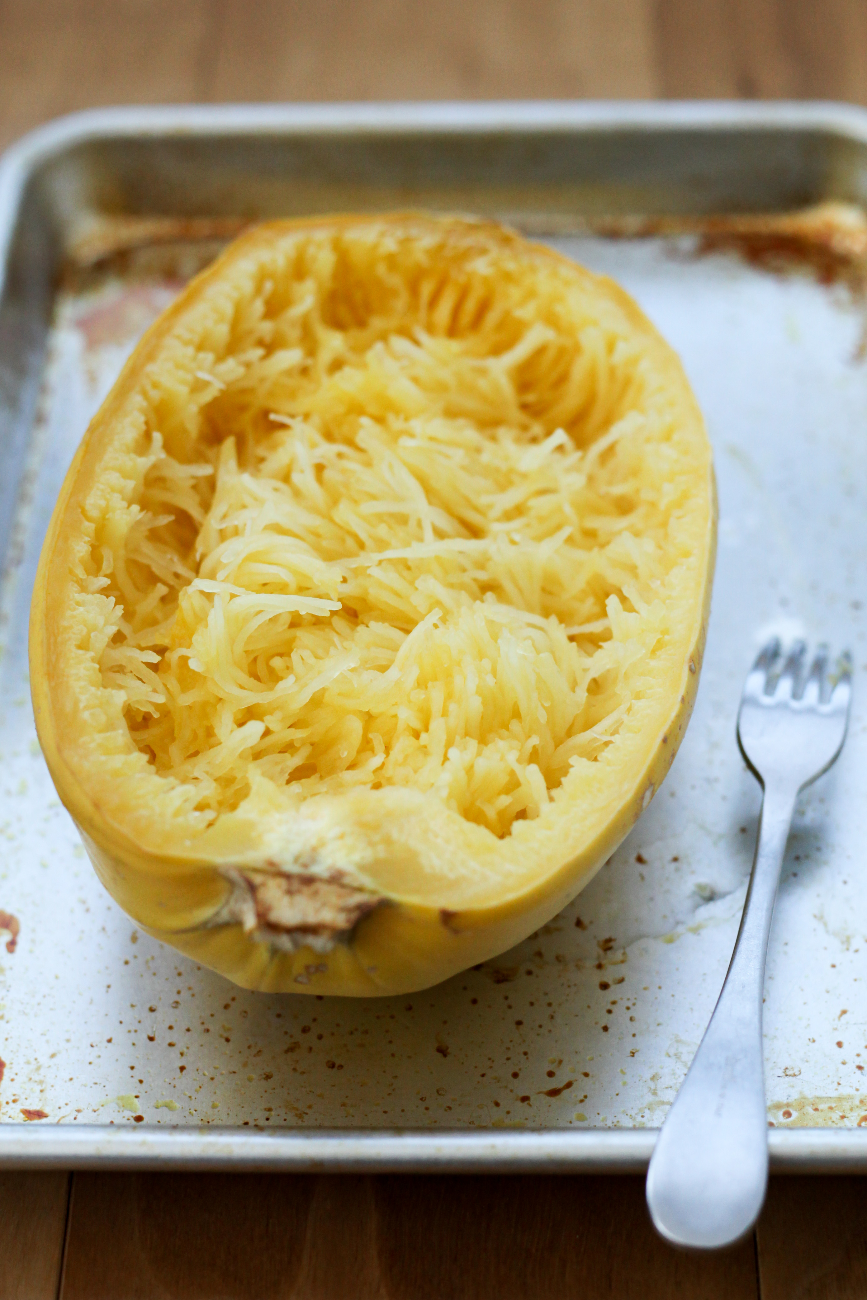 Scooping out spaghetti squash flesh